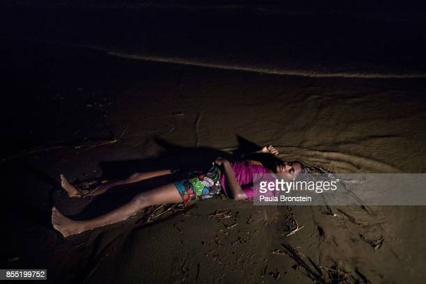 The body of a Rohingya woman lays on a beach washed up after a boat sunk in rough seas off the coast of Bangladesh carrying over 100 people September...