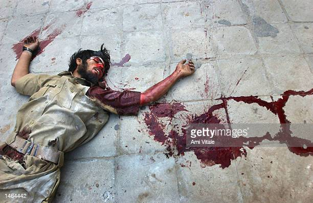 The body of a separatist militant disguised as policemen lies in a pool of blood October 8 2002 in Doda district of the Indian held state of Jammu...