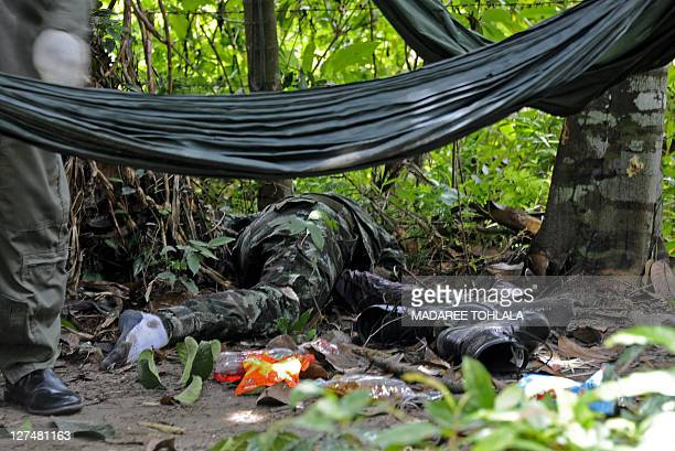 The body of a slain soldier lies on the ground after he was killed in a bomb and shooting attack at a school by suspected separatist militants in...