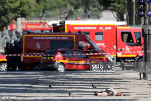 TOPSHOT The body of a suspect lies on a side path in a sealed off area of the ChampsElysees avenue on June 19 2017 in Paris with rescuers' cars in...