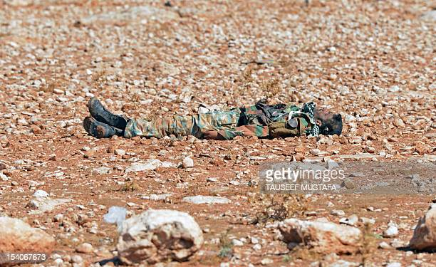 The body of a Syrian army soldier lies near the entrance of a military site in the city of al-Taana, near Syria's key battleground city of Aleppo, on...