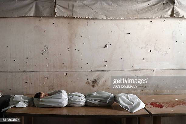 TOPSHOT The body of a Syrian child lies on a table at a morgue on October 5 following reported air strikes on the rebelheld town of Douma on the...
