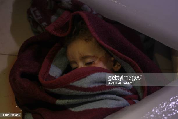 The body of a Syrian infant lies at a morgue following reported regime airstrikes on the town of Muhambal in the northern Idlib province on July 6...