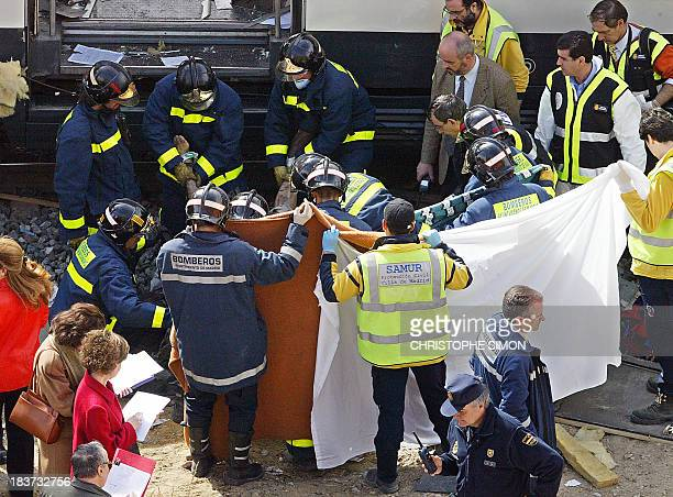The body of a victim is evacuated after a train exploded at the Atocha train station in Madrid 11 March 2004 At least 173 people were killed and some...
