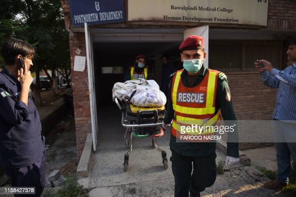 The body of a victim killed after a Pakistani Army Aviation Corps aircraft crashed into residential buildings is wheeled on a stretcher at hospital...