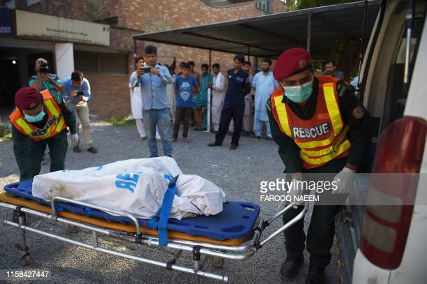The body of a victim killed after a Pakistani Army Aviation Corps aircraft crashed into a residential area is wheeled to a waiting ambulance at a...