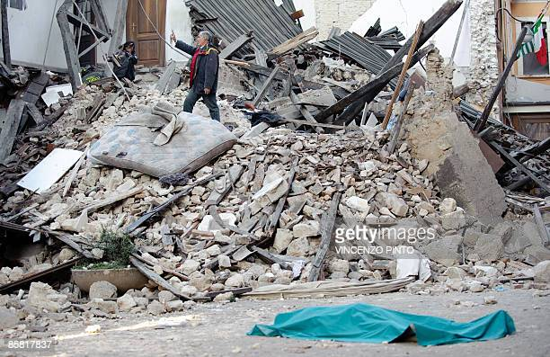 The body of a victim lies on the street on April 6, 2009 in front of his collapsed house in the center of the Abruzzo capital L'Aquila, the epicenter...
