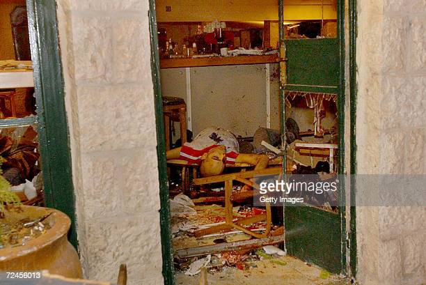 The body of a victim of a Palestinian suicide bombing lies where he died March 9 2002 in Jerusalems Moment coffee shop near the official residence of...