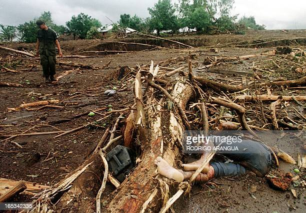 The body of a victim of the Posoltega mudslide 135kms northwest of Managua lies in a mudfield as a Nicaraguan army soldier inspects the area The...