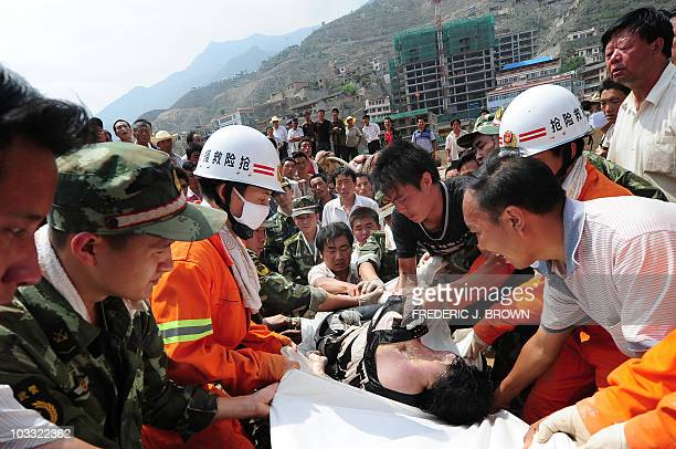 The body of a woman is pulled out from the mud by rescuers from the devastating landslide in Zhouqu on August 10, 2010 in northwest China's Gansu...