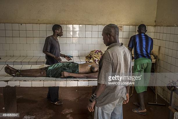 The body of a woman who died in the airport displaced camp overnight is prepared for burial in the morgue of the General hospital in Bangui on May 30...
