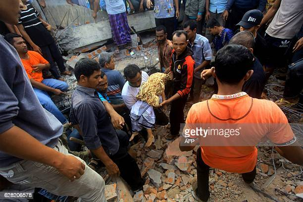 TOPSHOT The body of a young earthquake victim is carried in Pidie Jaya Aceh province on December 7 2016 At least 52 people died and dozens were...