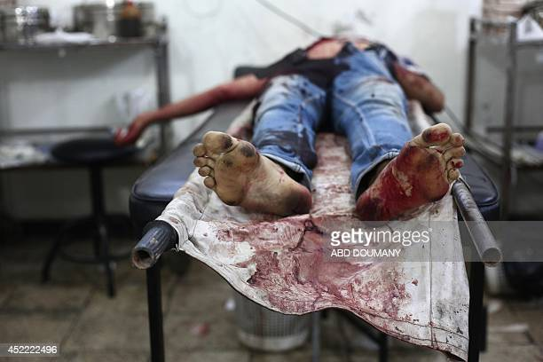 The body of a young man lies on stretcher brought into a makeshift hospital on July 16 following a reported air strike by the Syrian airforce and...