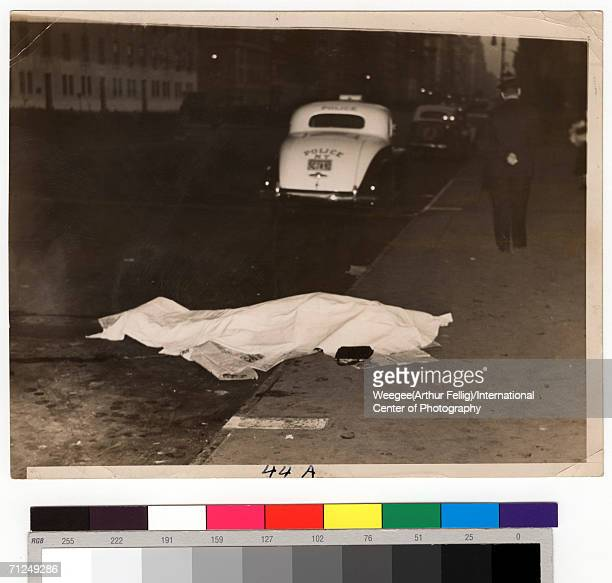 The body of a young woman who jumped from a car and was killed lies on the curb covered by newspapers and a sheet as a policeman walks away with his...