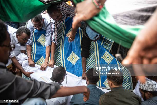 The body of Abdalla Mohamed Dahir is placed in a grave during a burial ceremony on January 16 2018 in Nairobi Kenya Dahir and his colleague were...