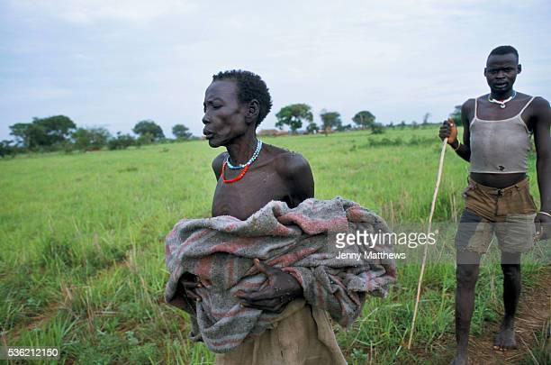 The body of Adut a two year old girl who died of malnutrition is carried wrapped in a blanket for burial by her grandmother accompanied by the grave...