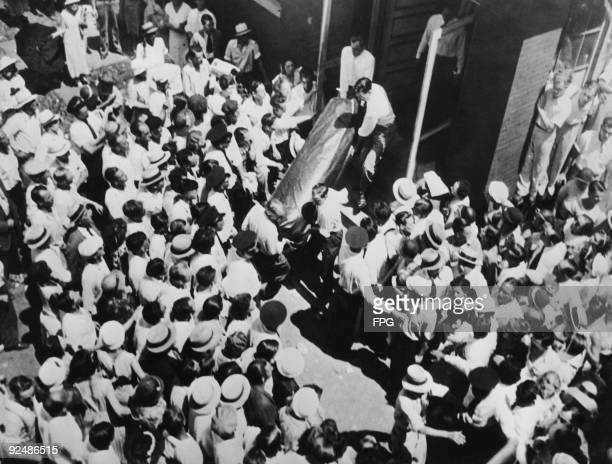 The body of American bank robber John Dillinger is brought out of a Chicago funeral home watched by a crowd of onlookers 24th July 1934 It will be...