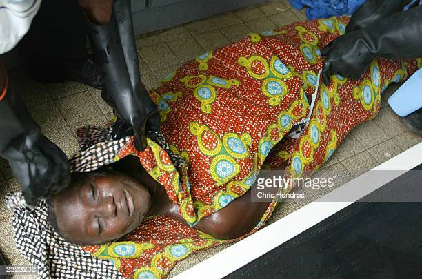 The body of an 18yearold girl shot in the head by a stray bullet the day before is zipped into a body bag July 29 2003 in Monrovia Liberia Gunfire...