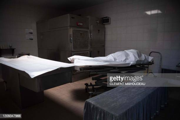 TOPSHOT The body of an 86yearold man lays covered with a sheet in the burial chamber of the ChateauneuflesMartigues cemetery southern France before...