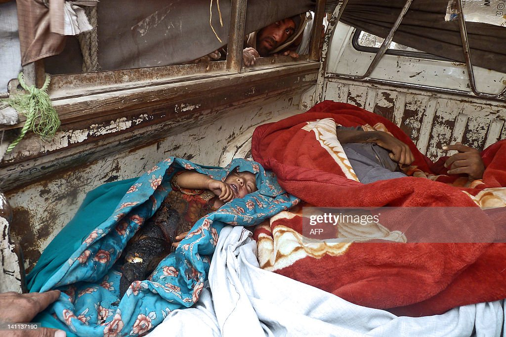 The body of an Afghan child, allegedly shot by a rogue US soldier, are seen with other bodies in the back of a truck in Alkozai village of Panjwayi district, Kandahar province on March 11, 2012. An AFP reporter counted 16 bodies -- including women and children -- in three Afghan houses after a rogue US soldier walked out of his base and began shooting civilians early Sunday. NATO's International Security Assistance Force said it had arrested a soldier 'in connection to an incident that resulted in Afghan casualties in Kandahar province', without giving a figure for the dead or wounded.