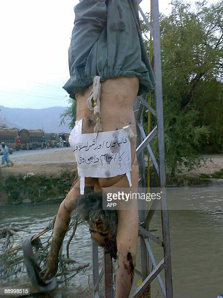The body of an alleged Taliban militant hangs from an electricity pole with a paper attached to his body bearing a slogan which translates as...