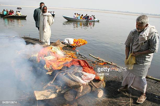 The body of an old woman is cremated on the banks of the Ganges River The priest on the right is sprinkling incense on the pyre