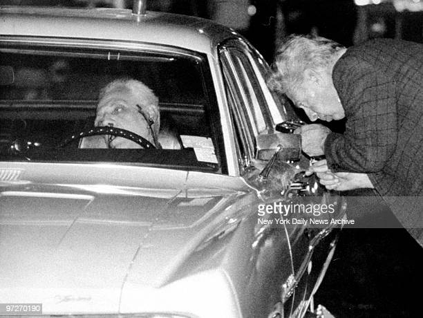 The body of Anthony Ricciardi slumps behind the wheel of his car as a policeman dusts for fingerprints in front of 84 Prospect Park