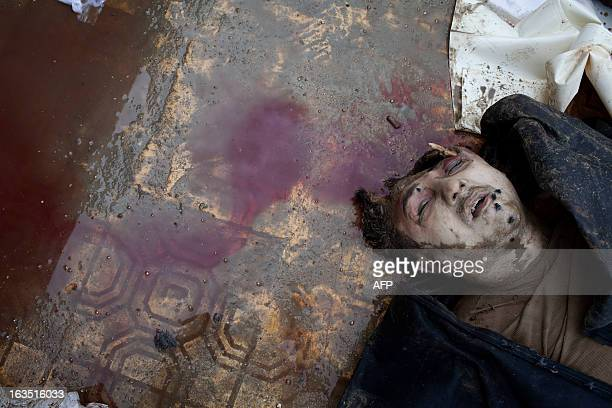 The body of civilian executed and dumped in the Quweiq river lies in the grounds of the courtyard of the Yarmouk School in the Bustan alQasr district...