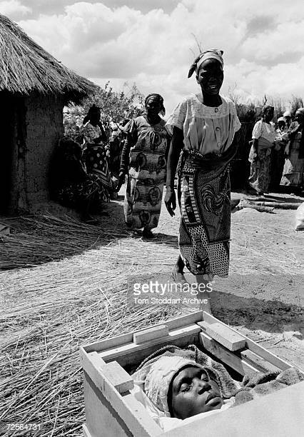 The body of Damaresi Chilengwa lies in a coffin outside her home in Shakatwa village Zambia Her husband died of AIDS one year before and she leaves...