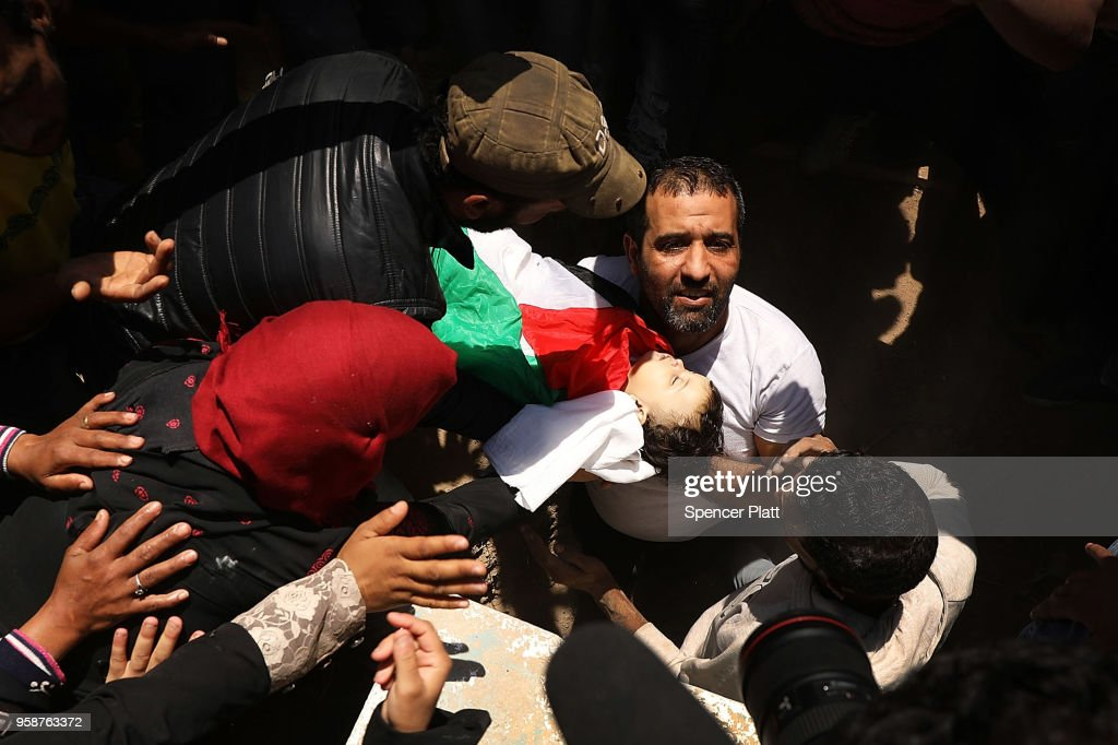 The body of eight-month-old Leila Anwar Ghandoor, who died in hospital on Tuesday morning from tear gas inhalation, is placed into a grave on May 15, 2018 in Gaza City, Gaza. Anwar was with a relative during the violence at the Gaza-Israel border yesterday when tear gas canisters were fired at crowds. Israeli soldiers killed over 50 Palestinians and wounded over a thousand as demonstrations on the Gaza-Israel border coincided with the controversial opening of the U.S. Embassy in Jerusalem. This marks the deadliest day of violence in Gaza since 2014. Gaza's Hamas rulers have vowed that the marches will continue until the decade-old Israeli blockade of the territory is lifted.