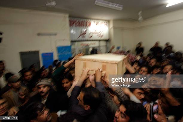 The body of former Prime Minister Benazir Bhutto is carried out of Rawalpindi General Hospital on December 27 2007 in Rawalpindi Pakistan The...