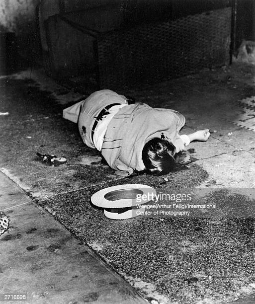 The body of gangster Dominick Didato also known as Terry Burns lies where he fell outside a restaurant on Elizabeth Street New York August 5 1936...
