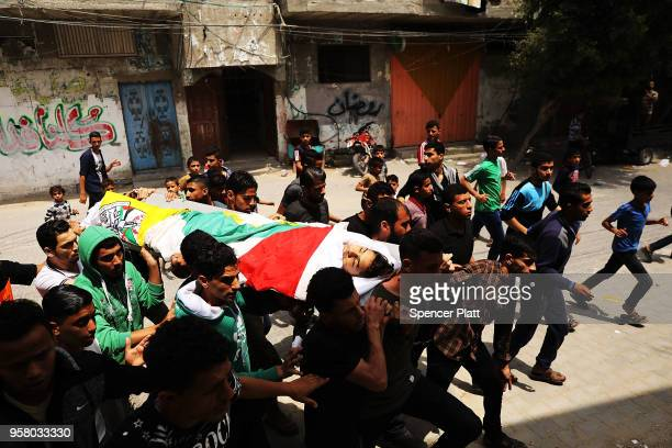 The body of Jamal Affana is brought through a Rafa, Gaza alleyway after he succumbed to a gunshot wound sustained during protests last Friday at the...