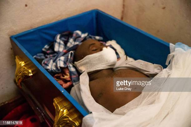 The body of John Bosco Tuhirirwe lies in a coffin with the shroud covering his body pulled back to reveal a bullet entry wound on November 13 2019 in...