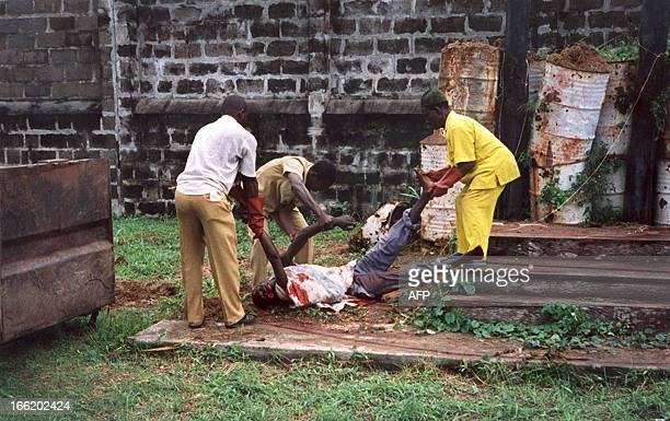 The body of one of the 43 prisoners who were sentenced to death is taken away after the mass execution by firingsquad before a crowd of 1000...