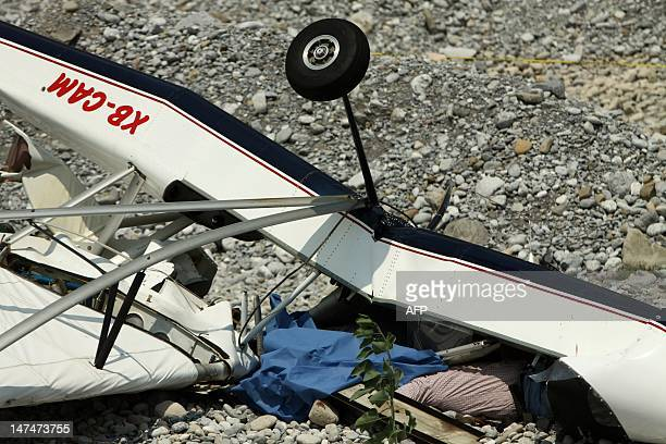 The body of one of the victims lies under the wreckage of a small plane that crashed in the municipality of Santa Catarina in Monterrey Nuevo Leon...