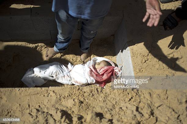 The body of oneyearold baby Noha Mesleh who died of wounds sustained after a UN school in Beit Hanun was hit by an Israeli tank shell is buried...
