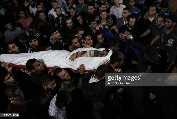 TOPSHOT The body of Palestinian Marwan Alagha is carried by mourners after he was killed when Israel blew up what it said was a tunnel stretching...