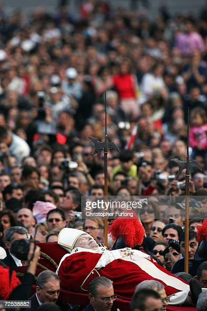 The body of Pope John Paul II makes its way past Polish flags to the Vatican carried by members of the Swiss Guard to be seen by thousands of...