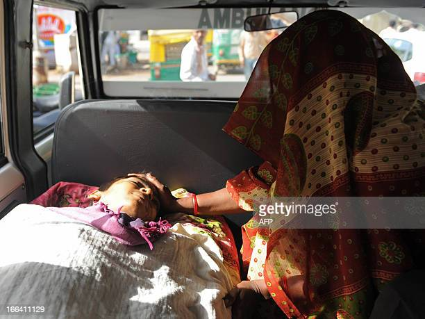The body of Rajubhai Ambubhai Bodana who succumbed to blood cancer is pictured in a van as his aunt mourns outside the Gujarat Cancer and Research...