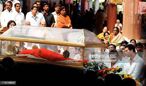The body of Sathya Sai Baba is displayed in a transparent as devotees including Indian cricketer Sachin Tendulkar pay their last respects to the...