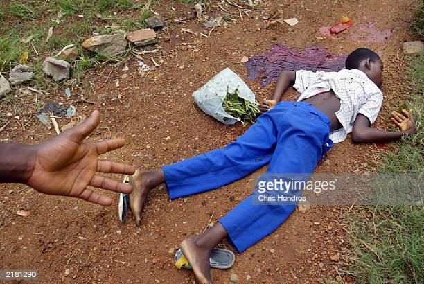 The body of school child Lasana Harding lies on a dirt path about two minutes after he was killed my a mortar shell July 21, 2003 in Monrovia,...