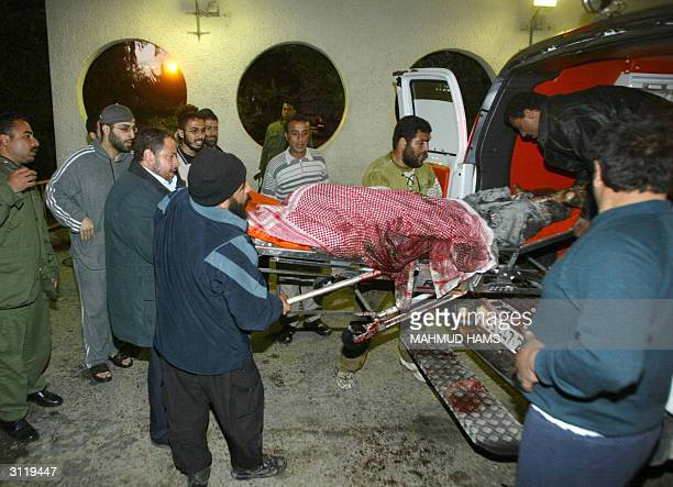 The body of Sheikh Ahmed Yassin the spiritual leader of the radical Hamas movement is carried out of an ambulance at Gaza City's alShifa hospital 22...