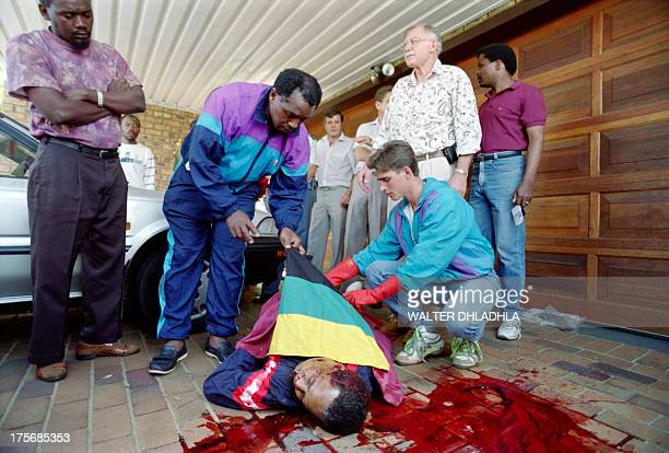 The body of South African Communist Party leader Chris Hani is covered with the African National Congress flag by Transvaal chairman Tokyo Sexwale as...
