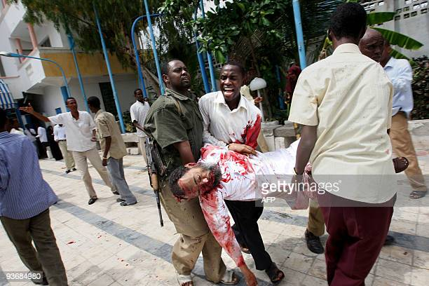 The body of the Somali Minister of Education Ibrahim Hassan Cadow is carried away from the scene of a suicide bomb attack during a university student...