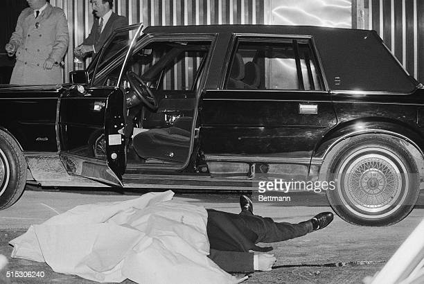 The body of Thomas Bilotti underboss to Paul Big Paul Castellano of the Gambino crime family lies alongside his car after being gunned down outside...
