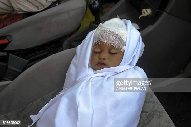 The body of twoyear old girl Zainab wrapped in a white shroud lies inside a car as it arrives at the Rijiyar Lemo cemetery in the northern Nigerian...