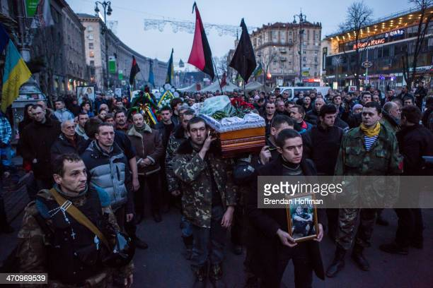 The body of Ustim Holodnyuk who was killed in fighting between antigovernment protesters and police is carried from Independence Square on February...