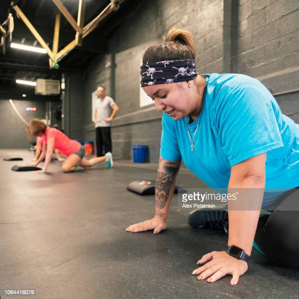 the body-positive athletic latino woman doing push-ups in the gym - alex potemkin or krakozawr latino fitness stock photos and pictures