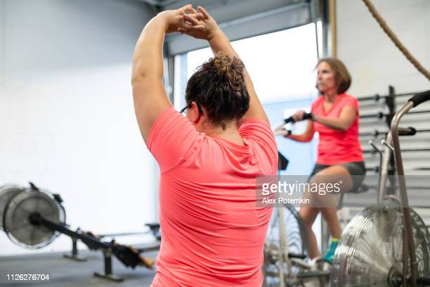 The body-positive attractive woman doing stretching exercise in the gym when the senior Latino woman cycling on the stationary bicycle